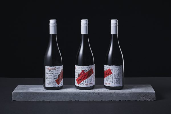 Untitled Wines - Three Bottles of the Red Blend on concrete plinth showing different angles of the label- Wine of New Zealand