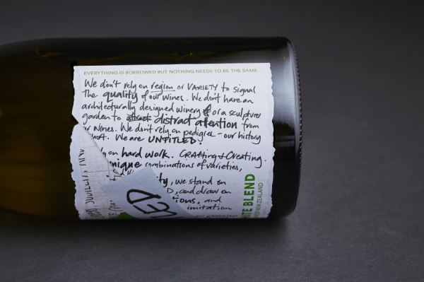 A bottle of Untitled's White Blend laying on side showing handwritten manifesto on wine label