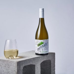 On a concrete block, there's a bottle of Untitled's White Blend with the wine in a stemless wine glass next to it.